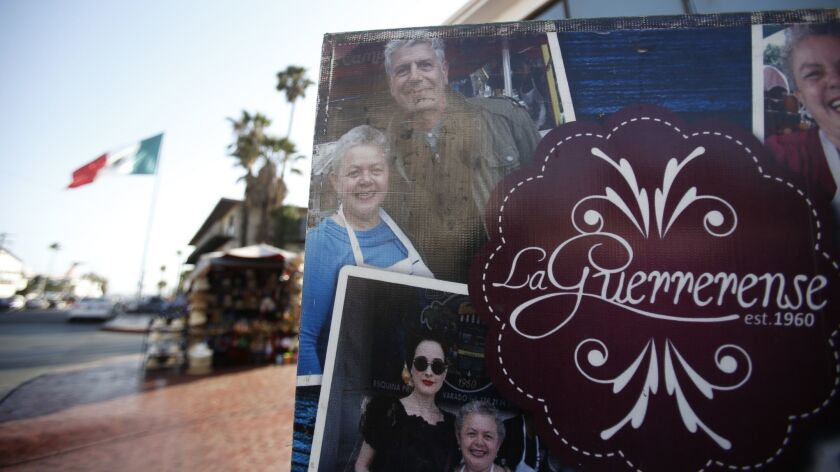 A poster at La Guerrerense in Ensenada shows owner Sabina Bandera with chef Anthony Bourdain, whose praise put the street food cart on the map.