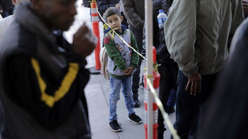 A boy looks on from a line where newly-arriving migrants enter their names into a list to apply for