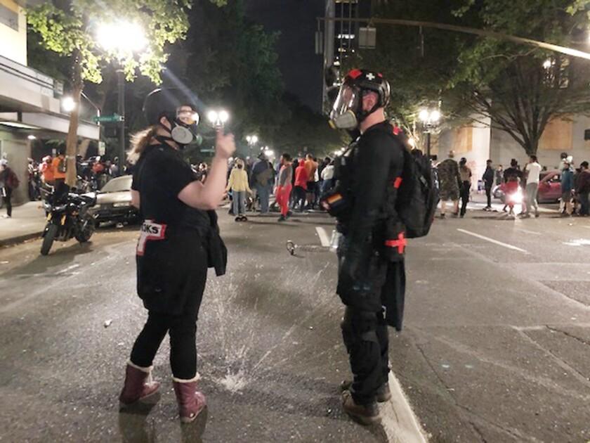 Brooke Hazel, left, gestures to fellow volunteer medic Davis Beeman after caring for a protester injured by tear gas.