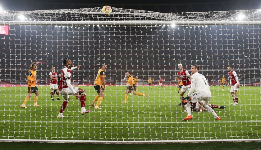 Wolverhampton Wanderers' Pedro Neto, centre, scores his team's first goal during the English Premier League soccer match between Arsenal and Wolverhampton Wanderers at Emirates Stadium, London, Sunday, Nov. 29, 2020. (Julian Finney/Pool via AP)