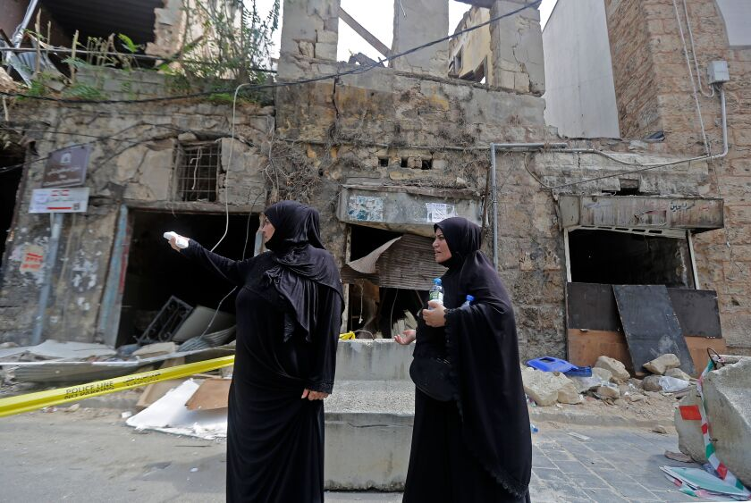 Two veiled women stand in front of a heavily damaged building following a chemical explosion at Beirut's port.