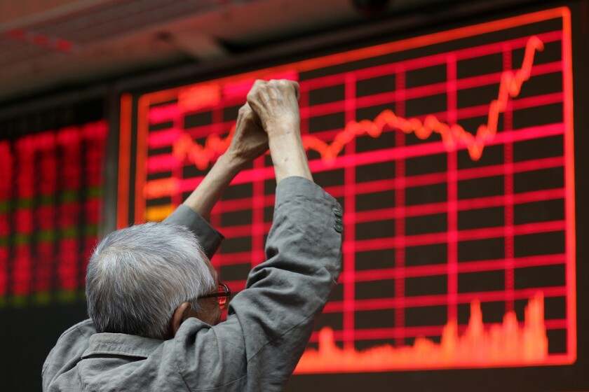 An investor reacts to a screen showing the stock composite index at a brokerage house in Beijing on Aug. 27.