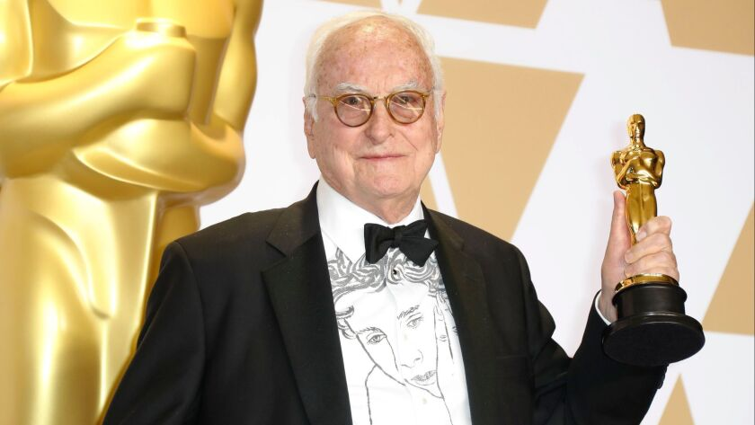 "James Ivory displays his Oscar for adapted screenplay -- ""Call Me by Your Name"" -- in the press room. His shirt is emblazoned with an image of Timothée Chalamet in the movie."