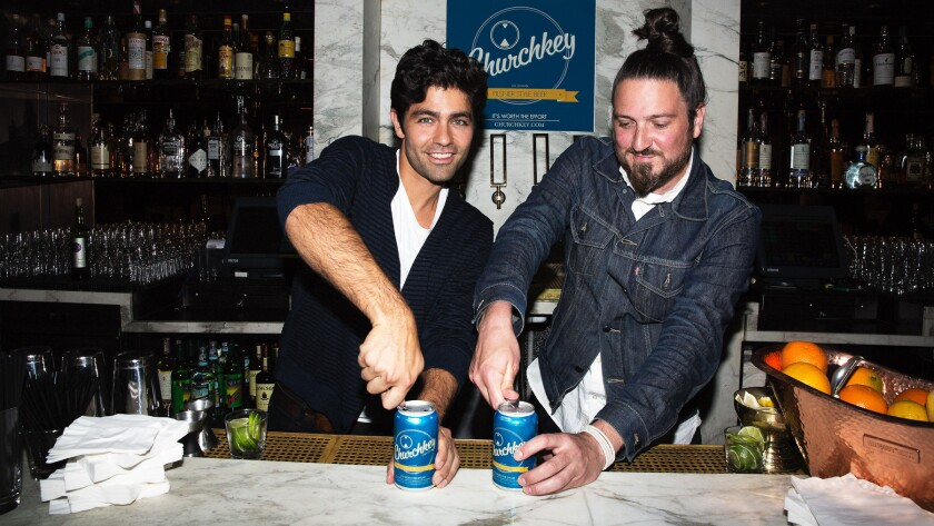 Churchkey founders Adrian Grenier and Justin Hawkins demonstrating the effort required to open their brand's flat top cans.