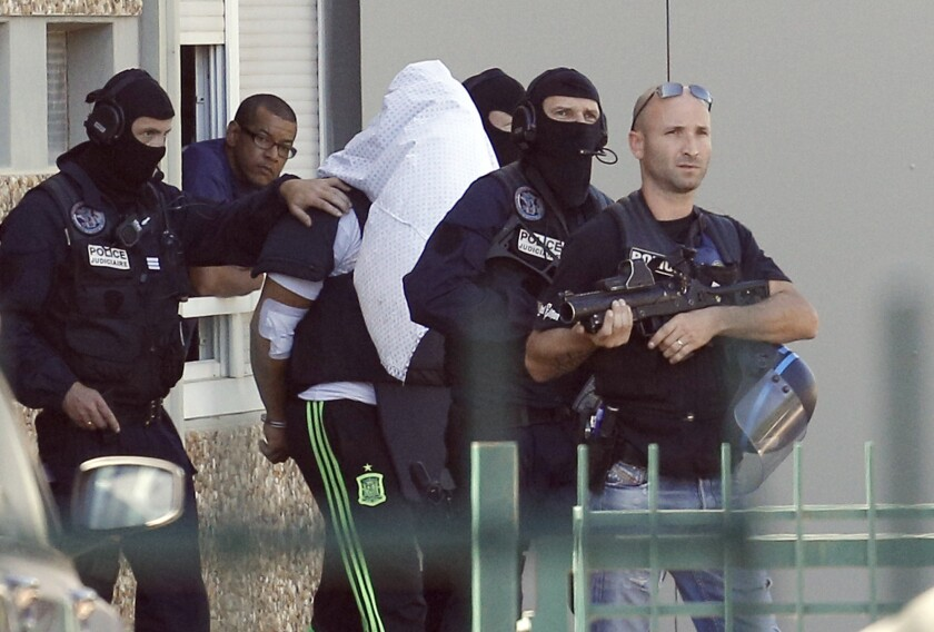 Yassin Salhi, the suspect in the beheading of a businessman, is escorted by police officers as they leave his home in Saint-Priest in central France on June 28, 2015.