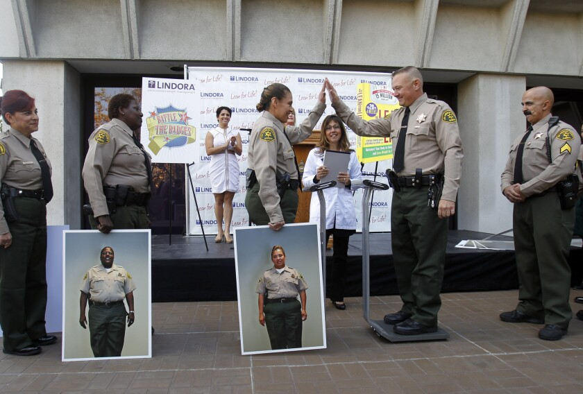 Los Angeles County Sheriff's Deputy Pearl Cruz, center, holding a portrait of herself before she lost 17.2% of her starting weight, congratulates Deputy Sheriff Brian Knott for his weight loss. [For the record: An earlier version of this caption incorrectly identified Deputy Sheriff Brian Knott as Sgt. Todd Knight.]
