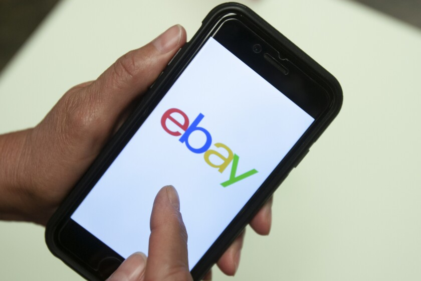 A person holds a smartphone displaying the EBay app