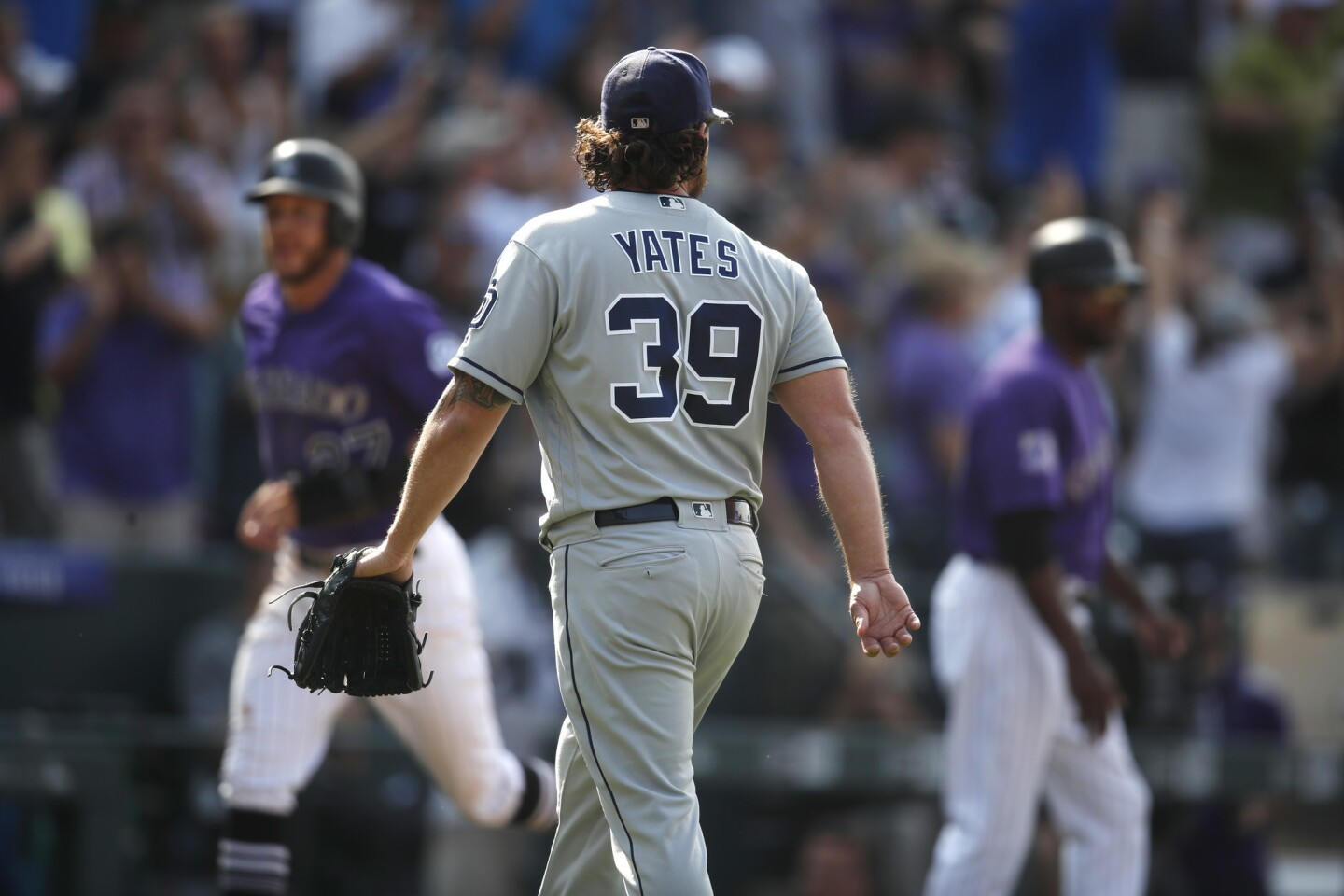 San Diego Padres relief pitcher Kirby Yates, front, heads to the dugout after giving up a two-run, walk off home run to Colorado Rockies' Ian Desmond in the ninth inning of a baseball game Thursday, Aug. 23, 2018, in Denver. The Rockies won 4-3. (AP Photo/David Zalubowski)