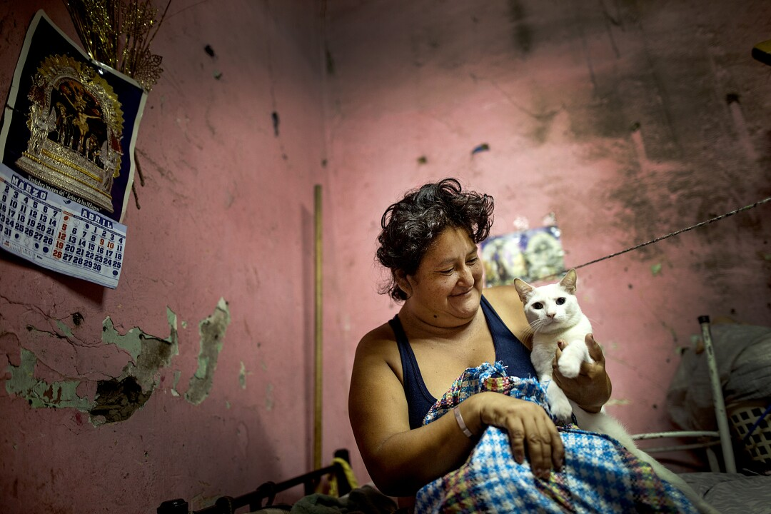 "PERU: Zulema Aguinaga smiles at her pet cat as she starts the day April 3 in her small room she shares with her son and elderly aunt, in a deteriorated house nicknamed ""Luriganchito,"" or ""Little Lurigancho,"" after San Pedro de Lurigancho, the country's most populous prison, in Lima, Peru."