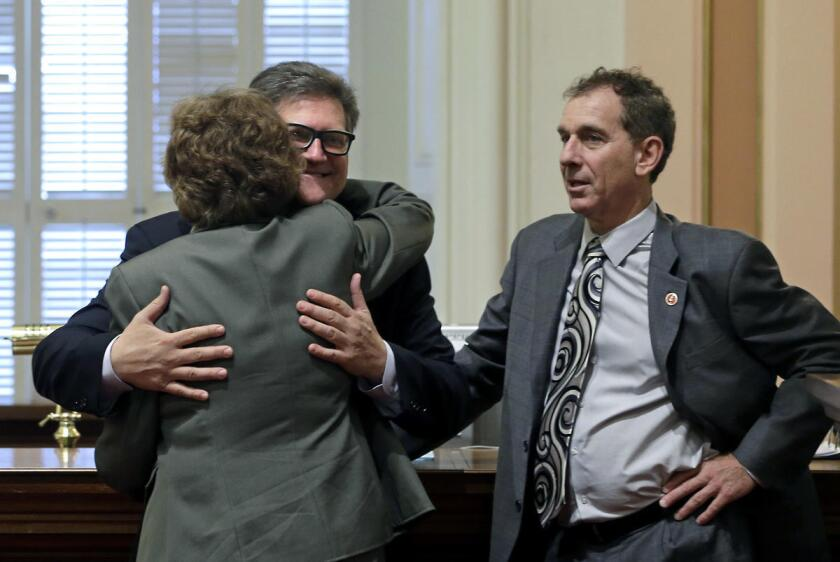 El senador estatal Bob Hertzberg (c), demócrata de Los Ángeles, abraza a su colega Lois Wolk, demócrata de Davis, enfrente del senador Bob Wieckowski, demócrata de Fremont, en Sacramento, California.