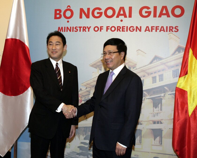 Japanese Foreign Minister Fumio Kishida, left, shakes hands with his Vietnamese counterpart Pham Binh Minh, right, as they pose for photos before their talks behind closed doors in Hanoi, Vietnam on Friday August 1, 2014. Japan said it will provide Vietnam six vessels as part of a grant aid package