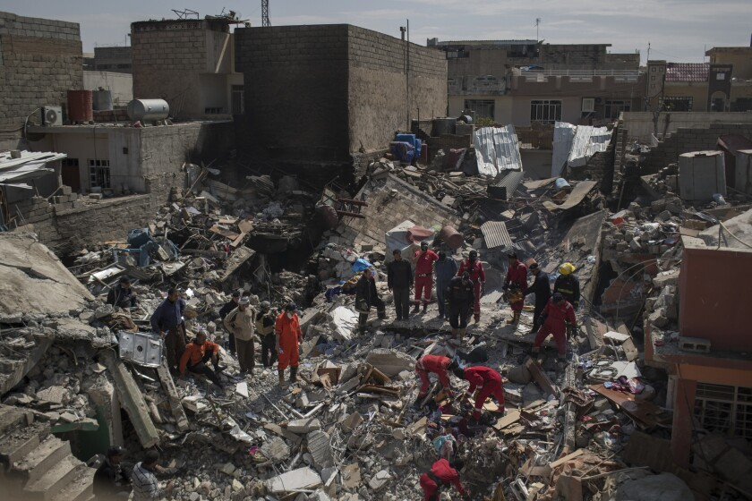 In this March 24, 2017, file photo, civil protection rescue teams work on the debris of a destroyed house to recover the bodies of people killed in an airstrike during fighting between Iraqi security forces and Islamic State militants on the western side of Mosul, Iraq.