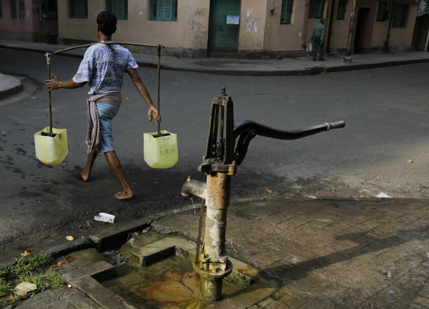 A water man or locally called as 'bhari' leaves to deliver water to houses after filling from a roadside hand pump while in Kolkata, India, Tuesday, March 22, 2016. A report says India has the world's highest number of people without access to clean water. The international charity Water Aid says 75.8 million Indians or 5 percent of the country's 1.25 billion population are forced to either buy water at high rates or use supplies that are contaminated with sewage or chemicals. (AP Photo/ Bikas Das)