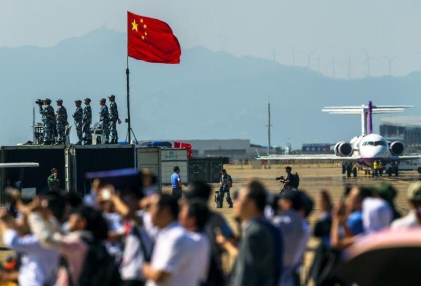 Visitantes observan la actuación de los aviones militares en una exhibición aérea realizada durante el primer día de la Duodécima Exhibición Internacional Aeronáutica y Aeroespacial de China. EFE/Archivo