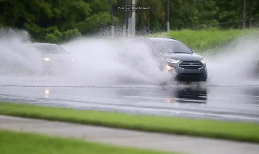 En esta imagen, tomada de un video, autos conducen por una carretera inundada en Canovanas