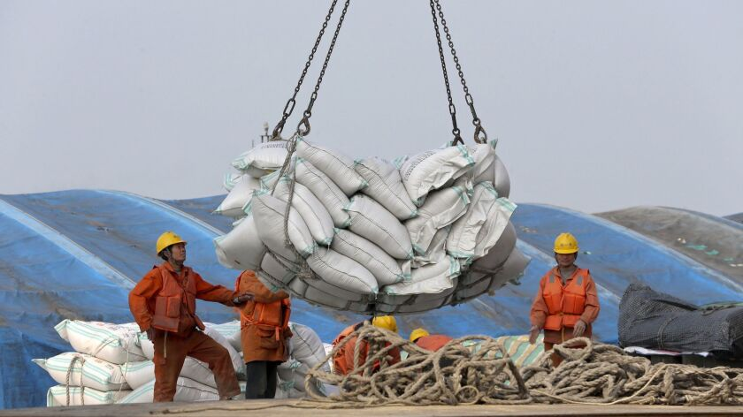 Workers load imported soybeans at a port in Nantong, China, on March 22.