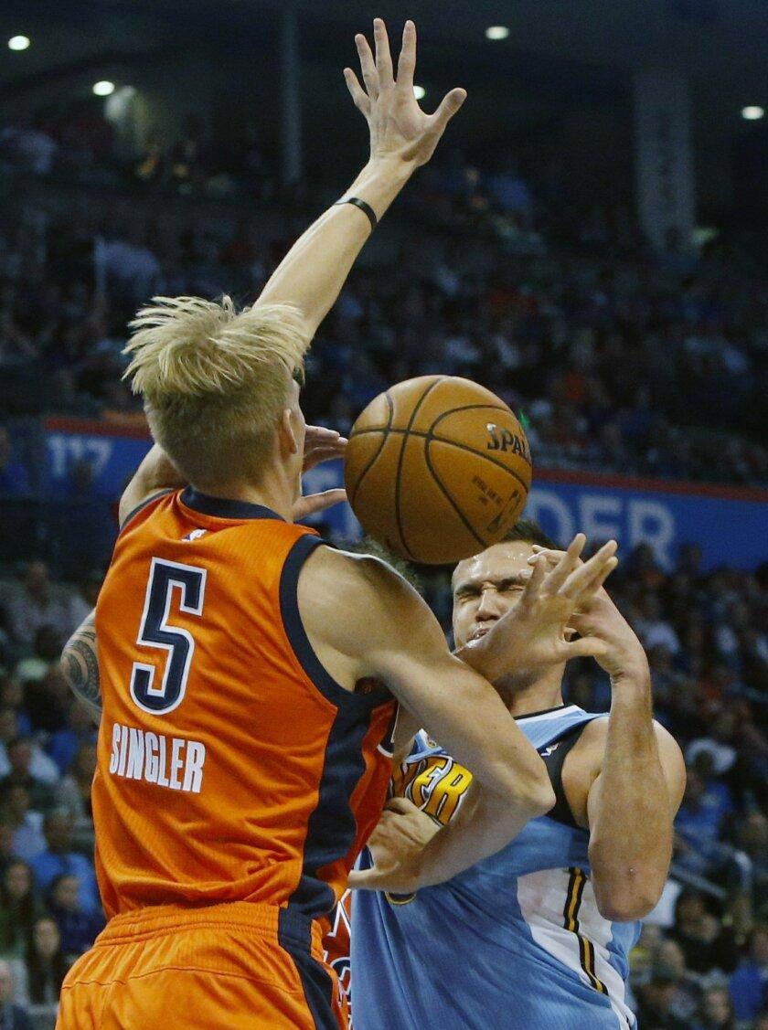 Oklahoma City Thunder forward Kyle Singler (5) and Denver Nuggets forward Danilo Gallinari, right, collide in the first half of an NBA basketball game in Oklahoma City, Sunday, Nov. 1, 2015. (AP Photo/Sue Ogrocki)