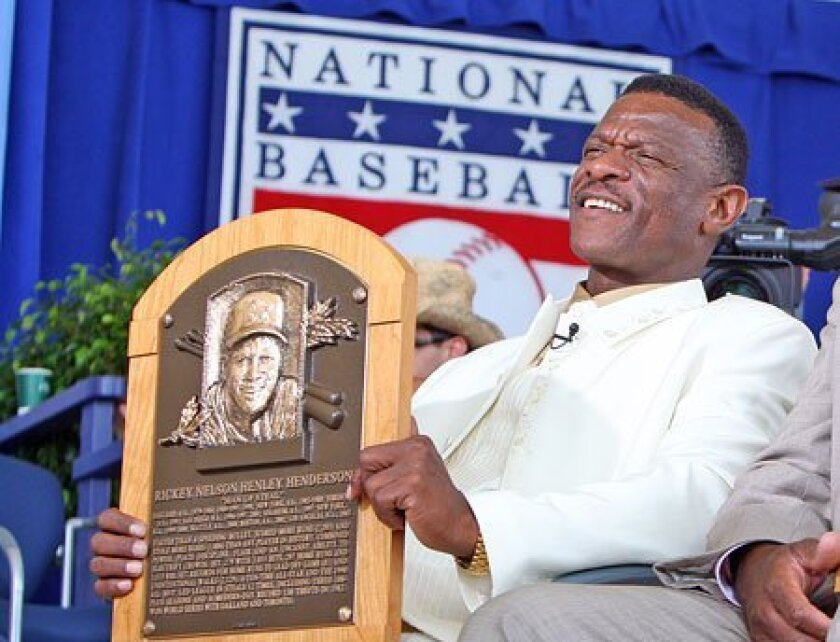 Rickey Henderson, baseball's all-time base stealer, holds his Hall of Fame plaque.   (Jim McIsaac / Getty Images)