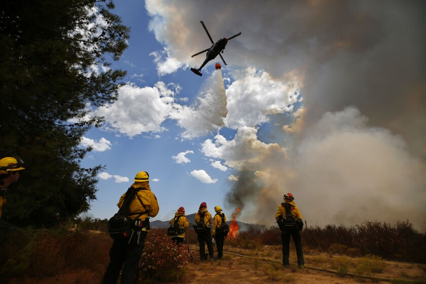 A helicopter makes a drop near on Montiel Truck Trail during the Valley fire on Sunday, Sept. 6, 2020