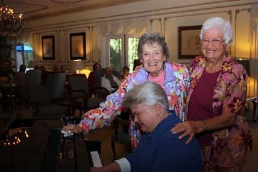 Leslie Miller plays a tune as Mary Wayne and Lois Clifton give her a pat on the back. Photo: Kathy Day