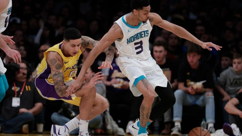 Lakers forward Kyle Kuzma, left, stumbles away possession of the ball as Charlotte Hornets guard Jeremy Lamb goes after it during second-half action at Staples Center on Friday.
