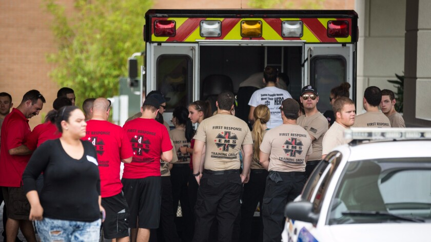 EMS personnel gather Sunday outside an Orlando hotel near the scene of the Pulse nightclub shooting.