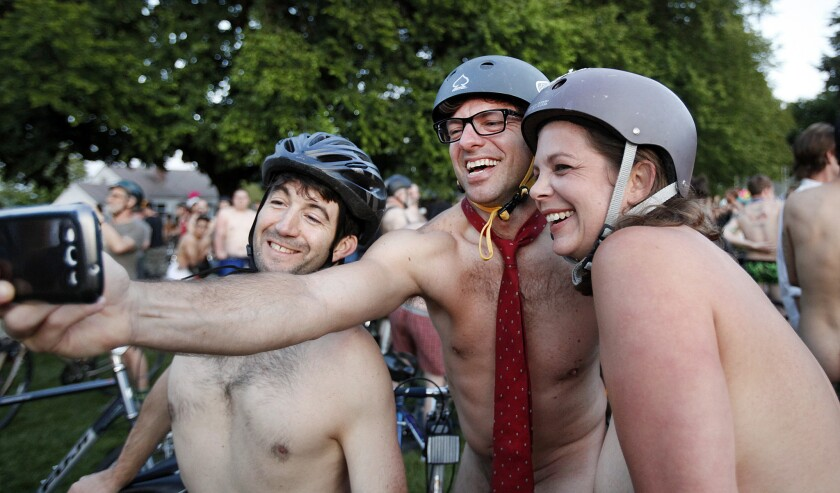 """Cyclists (from left) Randy Rodriguez, Chris Lynch and Mary Cadien take a """"selfie"""" wearing only a tie as they join thousands of others at Normandale Park in Portland, Ore., on Saturday for the 11th annual World Naked Bike Ride."""