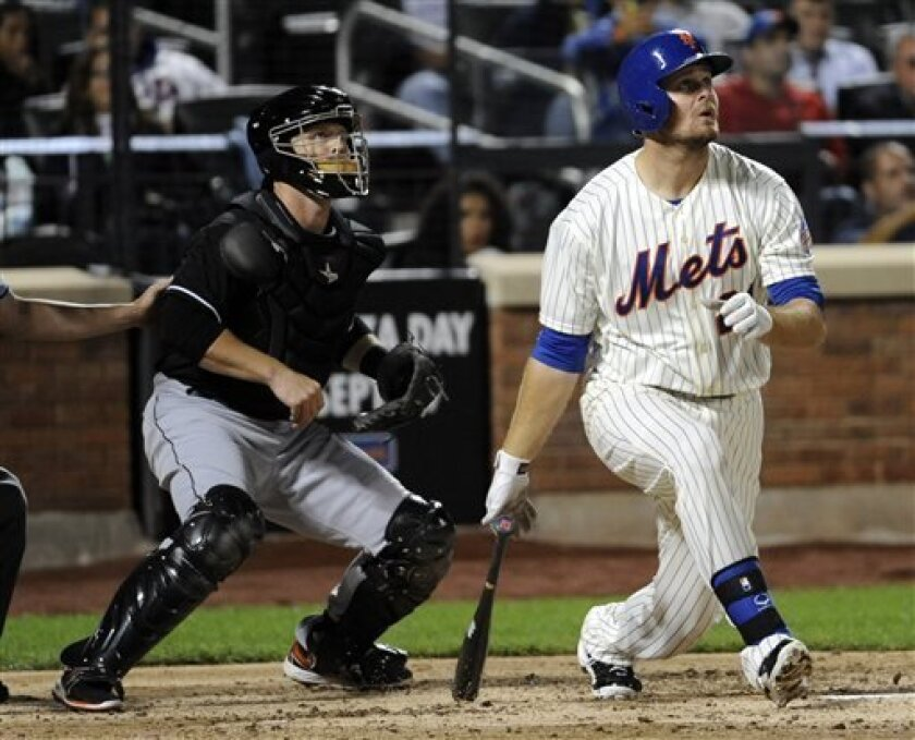 New York Mets' Lucas Duda, right, follows through on a three-run home run as Miami Marlins catcher Koyie Hill, left, looks on during the sixth inning of a baseball game on Friday, Sept. 13, 2013, in New York. (AP Photo/Bill Kostroun)