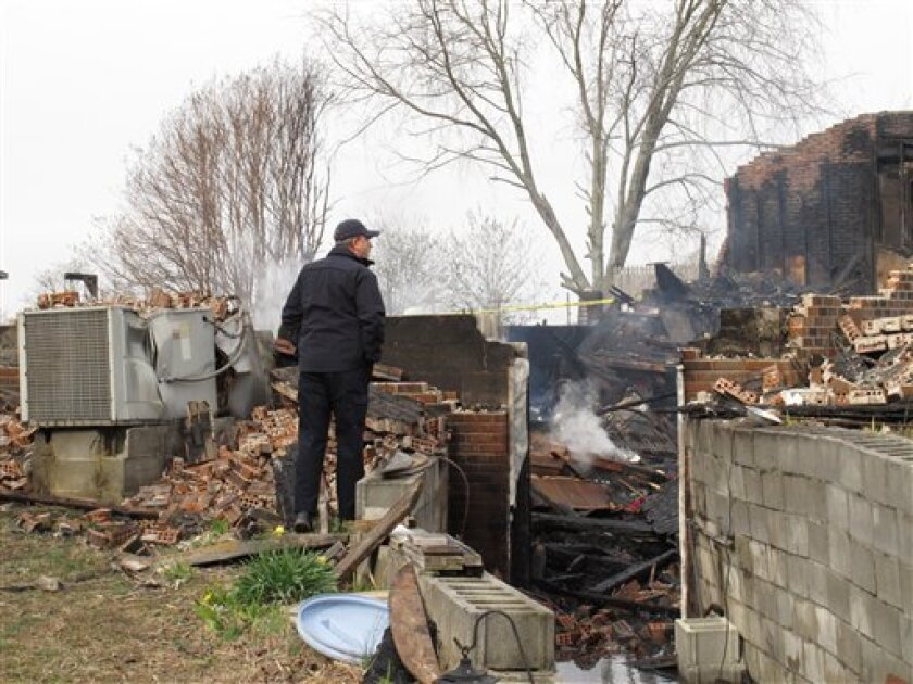 Dewey Woody Jr., director of the bomb and arson section of the Tennessee fire marshal's office, on Monday, March 4, 2013, looks at the smoldering debris of a fatal house fire in Lafayette, Tenn. Authorities say a Macon County man tried to save his three neighbors from the house fire, but all four were killed. (AP Photo/Kristin M. Hall)