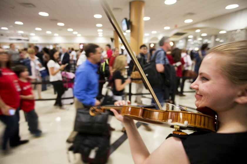 In this image made with a slow shutter speed, violinist Jennifer Warrilow plays for travelers moving through a security checkpoint line at Hartsfield-Jackson Atlanta International Airport, Thursday, May 19, 2016, in Atlanta. The airlines have a message for fliers: Get to the airport early. Long lin