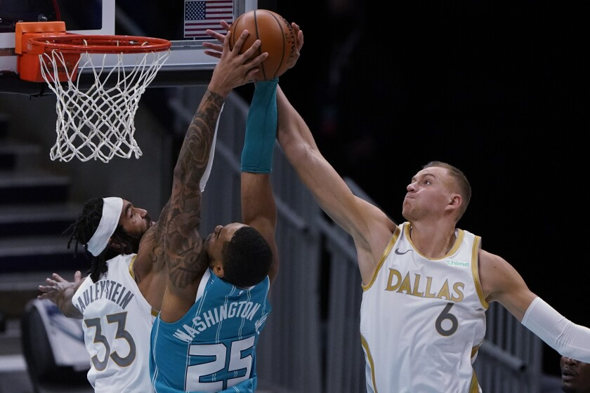 Dallas Mavericks' Kristaps Porzingis, right, blocks a shot by Charlotte Hornets forward P.J. Washington as center Willie Cauley-Stein defends during the second half of an NBA basketball game in Charlotte, N.C., Wednesday, Jan. 13, 2021. (AP Photo/Chris Carlson)