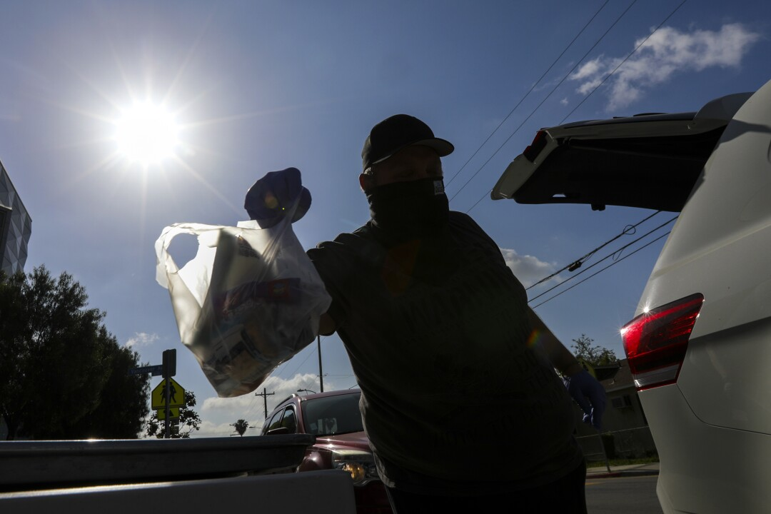 A man grabs meal bags distributed by LAUSD James A. Garfield High School in Los Angeles