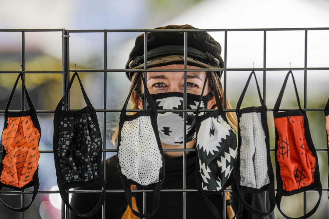 Alisun Franson sells face masks from a stand in front of her business Amiga Wild in Venice.