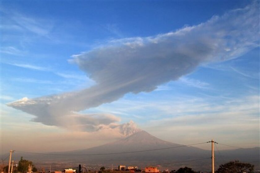 A large plume of ash rises from the Popocatepetl volcano as seen from the highway to Atlixco, Mexico early Friday June 3, 2011. The 17,886-foot (5,450-meter) mountain shot a blast of ash about 2 miles (3 kilometers) above its crater but there is no report of threat to populated areas. (AP Photo)