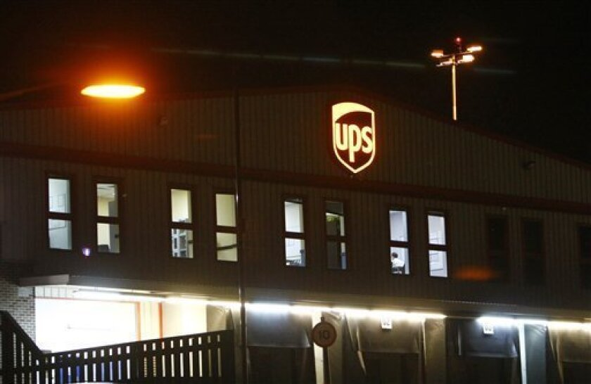 FILE - In this Friday, Oct. 29, 2010, file photo the UPS building at the East Midlands airport, Derby, England, is seen after UPS cargo containers were searched by British police. When a UPS plane, carrying an explosive package from Yemen, landed it was just after 10 p.m. in Washington and 3 a.m. Friday in England. Tipped off, police searched the plane, even the explosive-laden-printer, for hours but found nothing. (AP Photo/Tim Hales, File)