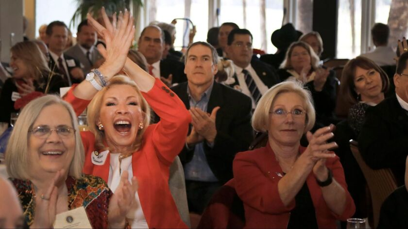 Supporters of President Donald Trump at the Fairbanks Ranch Country Club Friday morning cheer as they watch him give his inaugural address after taking oath of office, becoming the 45th president.