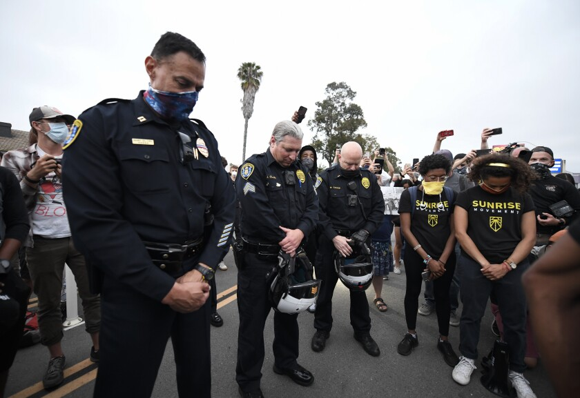 San Diego police officers bow their heads in prayer with demonstrators at a racial justice protest in Point Loma.