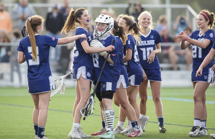 Newport Harbor girls' lacrosse players celebrate their 13-7 win over Corona del Mar during a Sunset League match on Tuesday.