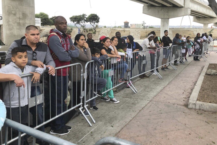 """FILE - In this Sept. 26, 2019 file photo asylum seekers in Tijuana, Mexico, listen to names being called from a waiting list to claim asylum at a border crossing in San Diego. Attorneys for the Trump administration and the American Civil Liberties Union have dueled before a federal appeals court on two major policies that rewrite rules for seeking and getting asylum. A three-judge panel of the 9th U.S. Circuit Court of Appeals heard arguments Tuesday, Oct. 1, 2019, in San Francisco on a policy to make asylum seekers wait in Mexico while their cases wind through U.S. immigration courts. More than 42,000 people have been returned to Mexico since January, when the policy officially known as """"Migrant Protection Protocols"""" took effect. (AP Photo/Elliot Spagat,File)"""