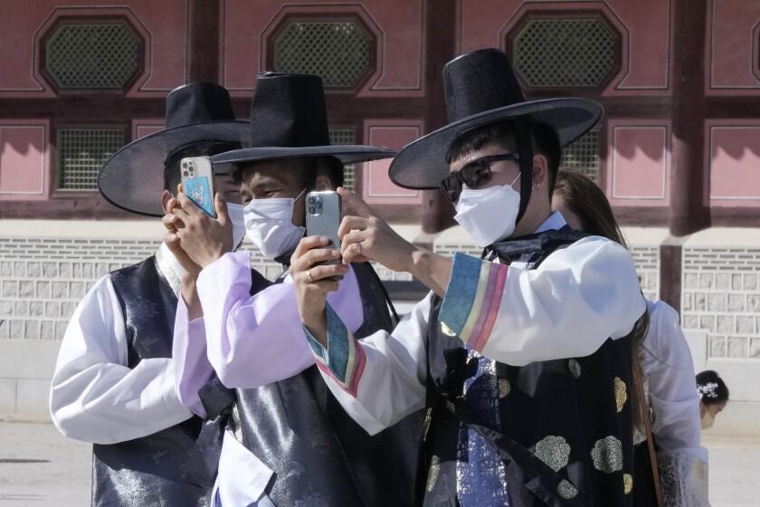 Un grupo de hombres, con mascarilla para protegerse del coronavirus, toman fotografías