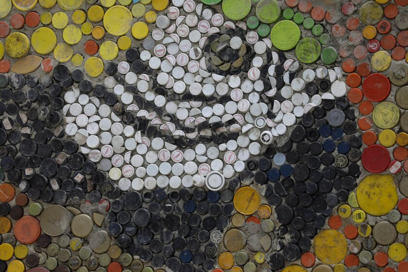 Plastic bottle caps form the face of a macaw within a large mosaic by Venezuelan artist Oscar Olivares in El Hatillo on the outskirts of Caracas, Venezuela, Thursday, Jan. 30, 2020. Olivares, 23, is using thousands of plastic bottle caps to create this mural which he started when he was just 14. (AP Photo/Ariana Cubillos)