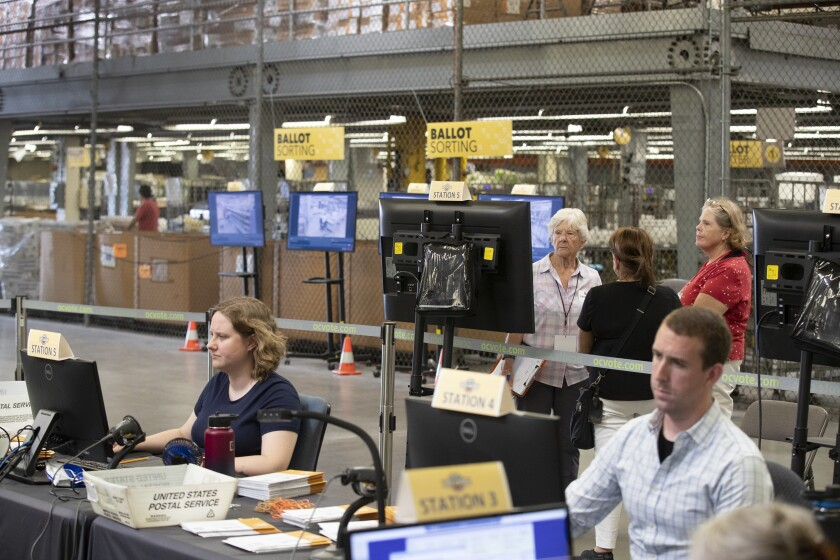 Observers from the Election Integrity Project watch ballots being processed in Orange County.