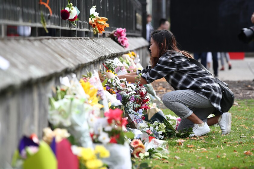 A mourner lays flowers outside the Botanic Gardens in Christchurch.