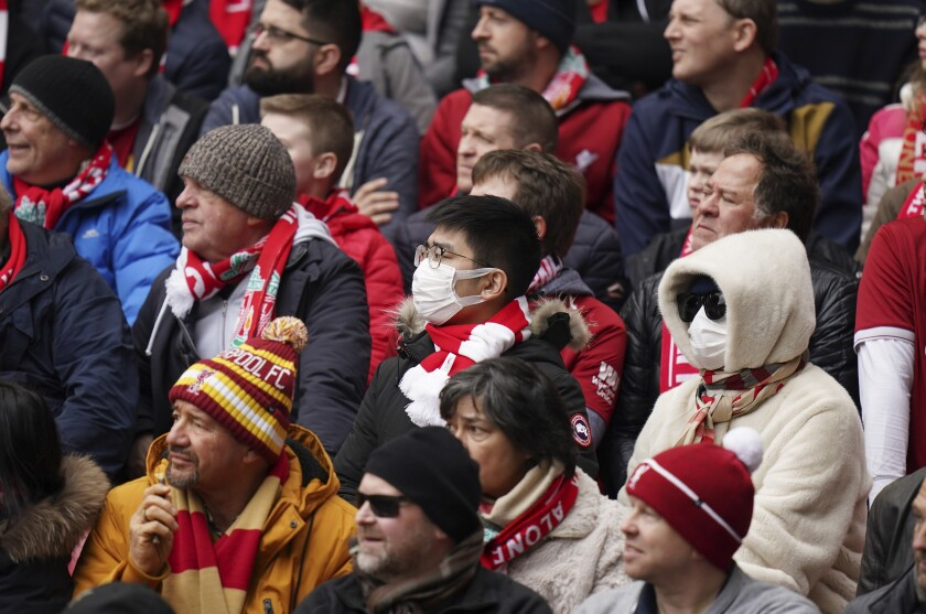 A fan wearing a protective mask attends at the English Premier League soccer match between Liverpool and Bournemouth at Anfield stadium in Liverpool, England, Saturday, March 7, 2020. (AP Photo/Jon Super)