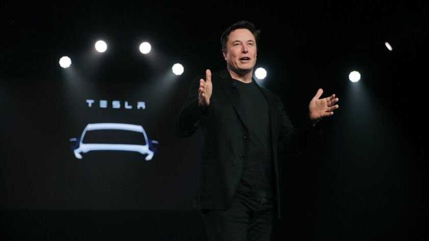 """Tesla chief Elon Musk in March, showing off a crossover Model Y. It was unclear where the capital to build the car would come from as Musk embarked on a """"hardcore"""" cost-cutting drive to meet current expenses."""