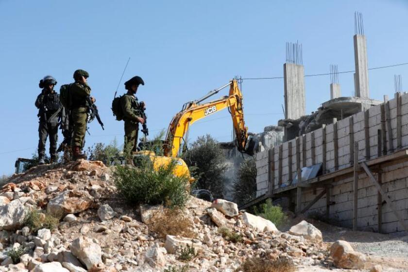 Varios soldados israelís montan guardia mientras una excavadora israelí procede a la demolición de una casa palestina en el pueblo de Walajeh, cerca de Belén (Cisjordania), hoy, 3 de septiembre de 2018. EFE