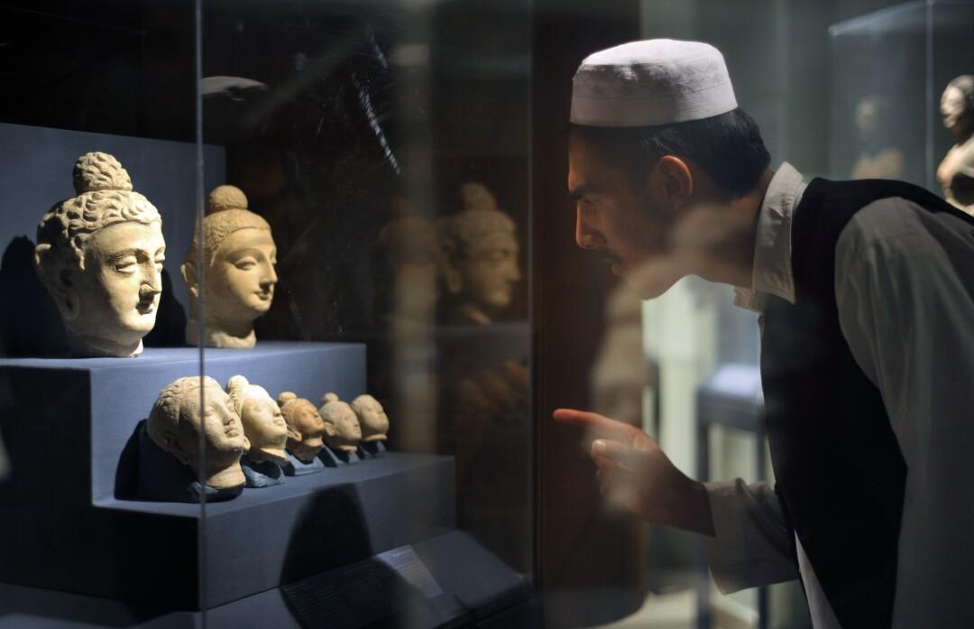 An Afghan student scrutinizes a display of Buddha in a glass vitrine