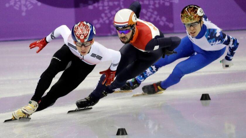 Lim Hyojun, left, holds off Sjinkie Knegt, center, and Semen Elistratov en route to winning the men's 1,500-meters short-track speedskating final on Saturday.