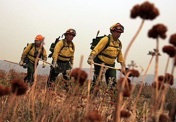 "Fire crews from New Mexico cut a fire line in Juniper Hills to keep the Station fire from spreading. Overnight Saturday, the blaze grew to 157,220 acres, making it the 10th-largest fire in modern California history, fire officials said. The fire was 51% contained. A large plume of smoke drifted into the areas of Juniper Hills and Littlerock, and Incident Commander Michael Bryant said the fire was about five miles from Juniper Hills. ""We want our communities not to panic,"" Bryant said. Fire officials said the fire's jump of the Angeles Crest Highway also threatened several structures."