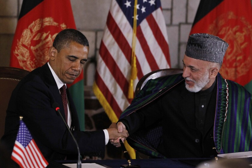 President Obama and then-President Hamid Karzai prepare to sign a strategic partnership agreement at the presidential palace in Kabul on May 2, 2012.